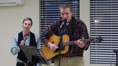 Ches and Robert sing and play guitar for the crowd at an Arc Community Celebration