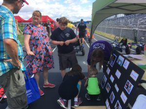 Mother and son speak with volunteers at the Arc tent at EFFORT Day, at the Christiansburg High School track.