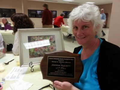 Johnna Elliott, recipient of the Renee Brown Award holds up her plaque for the camera.